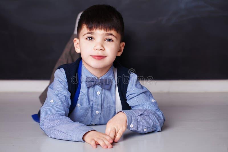 在家看照相机的蓝色衬衣的微笑的小男孩 免版税库存图片
