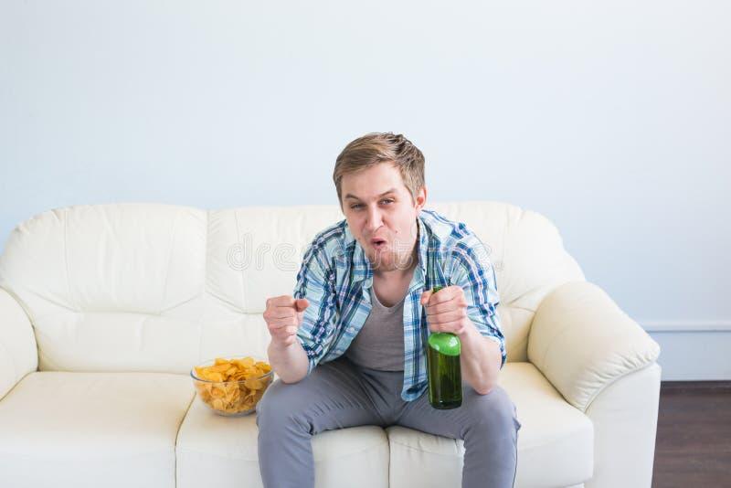 在家看电视的人用啤酒和芯片 库存图片