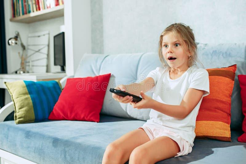 在家看电视的小偶然女孩 女性孩子坐有电视遥控和交换的渠道的沙发 库存照片