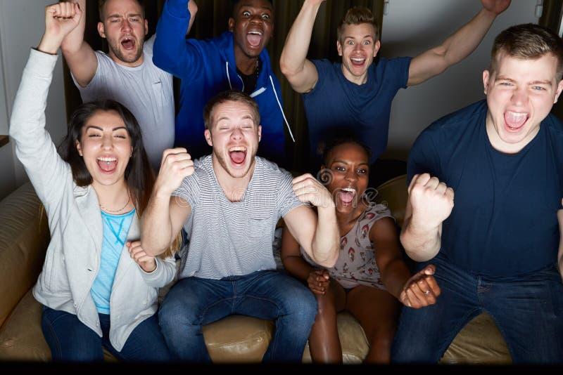 在家看电视的小组朋友一起 库存照片