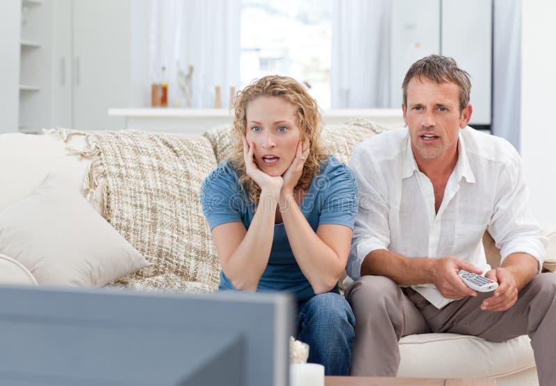 在家看电视的恋人在客厅 免版税库存照片