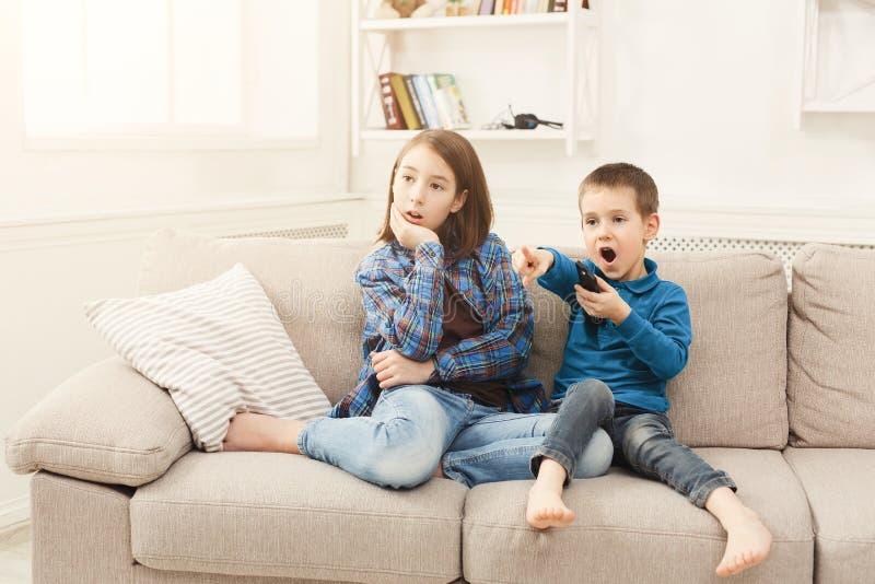 在家看电视的惊奇孩子 免版税库存照片
