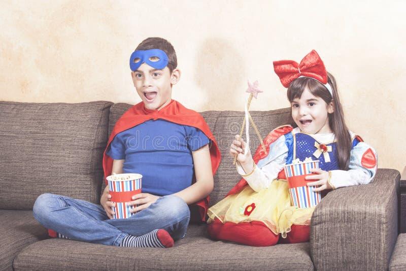 在家看电视的愉快的孩子 库存照片