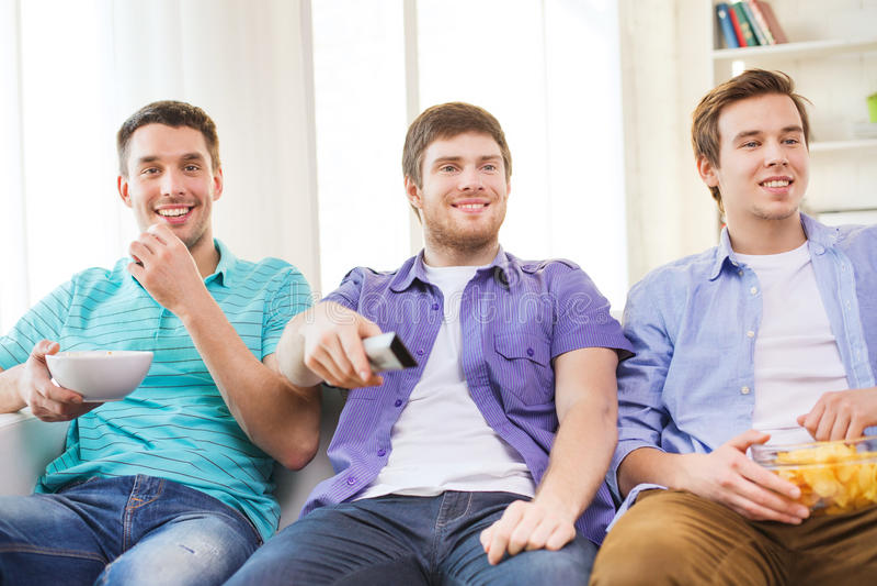 在家看电视的愉快的男性朋友 免版税库存图片
