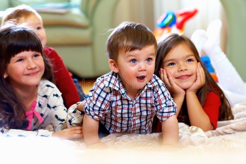 在家看电视的组愉快的孩子 免版税库存图片
