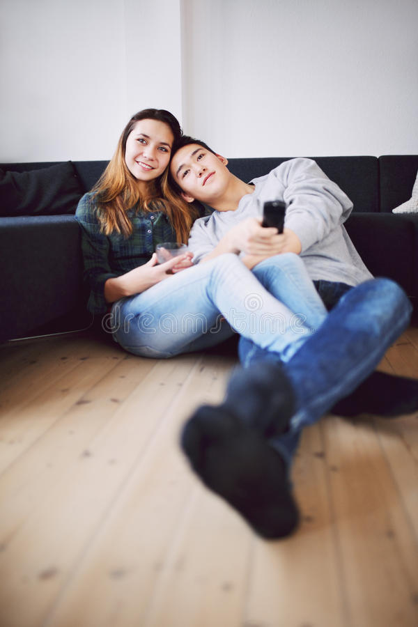 在家看电视的轻松的少年夫妇 免版税库存照片