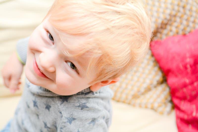 在家看直接地照相机的愉快的孩子 逗人喜爱的白肤金发的男孩微笑着 库存照片