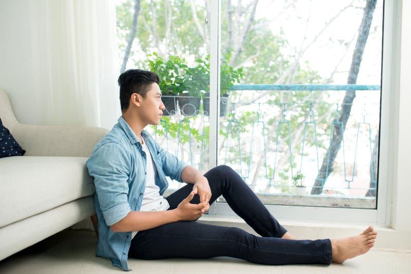 在家看窗口的体贴的亚裔人 库存图片