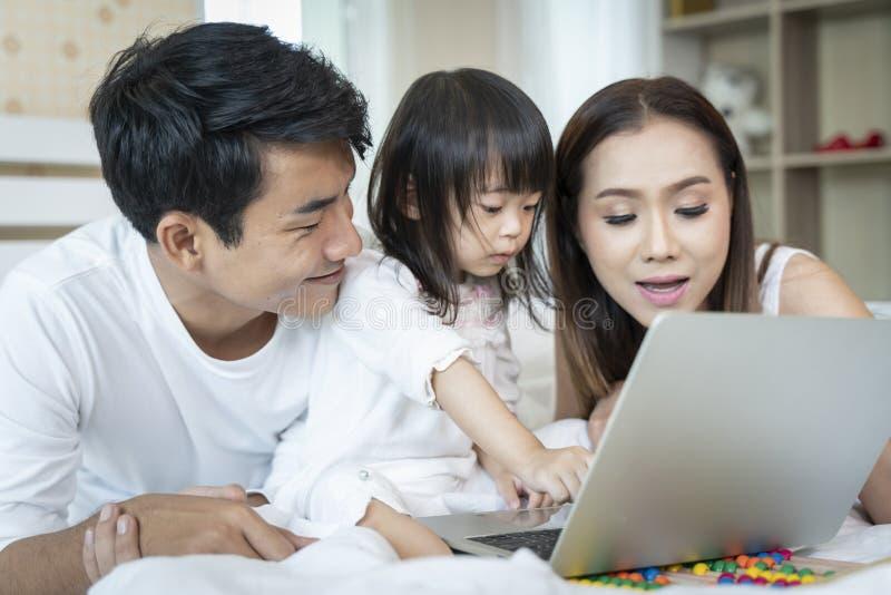 在家看膝上型计算机的家庭 免版税库存图片