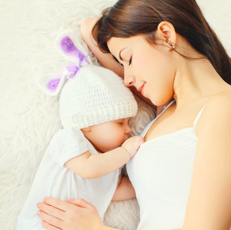 在家睡觉与在床上的婴孩的特写镜头愉快的年轻母亲 免版税库存图片