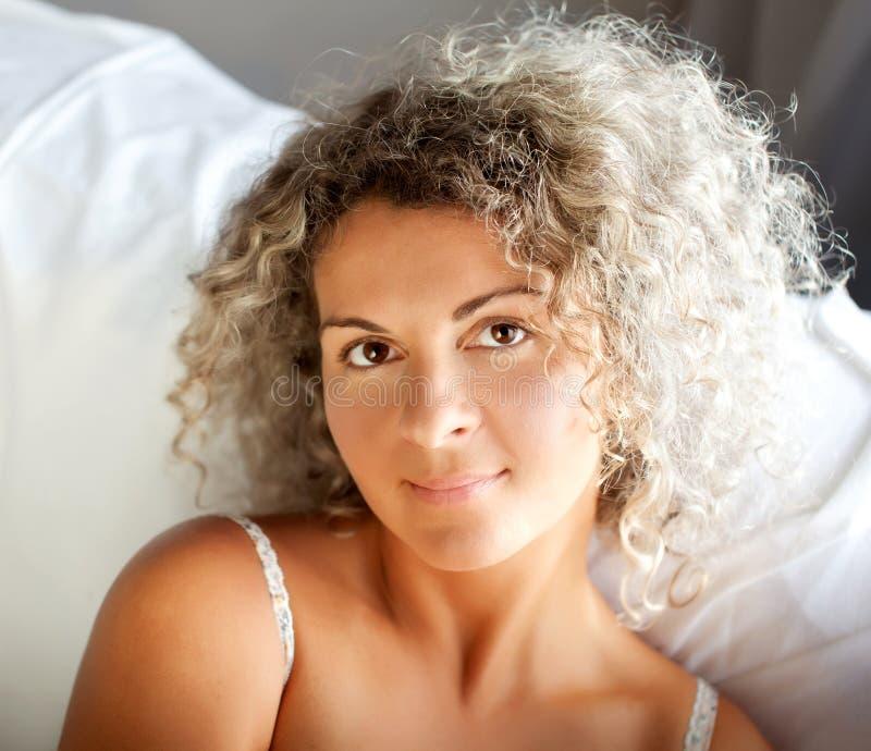 在家睡觉在她的床上的妇女 免版税库存照片