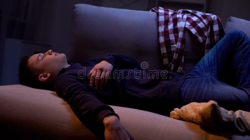 在家睡觉在晚上的被用尽的少年学生,消磨时间和朋友一起 库存照片