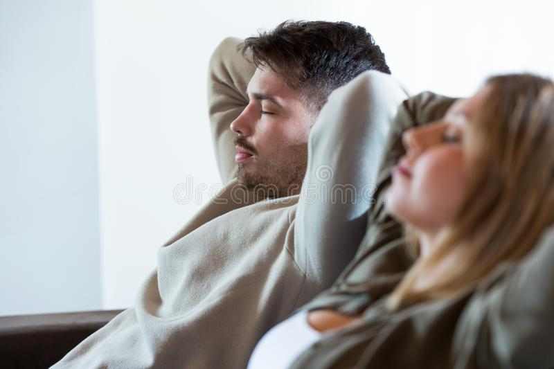 在家睡觉在沙发的美好的年轻轻松的夫妇 库存图片