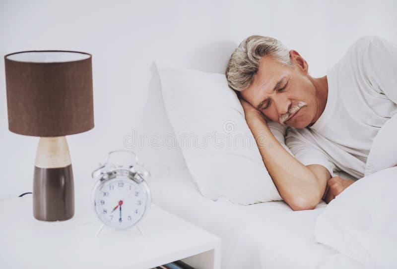 在家睡觉在舒适的白色床上的老人 免版税库存图片