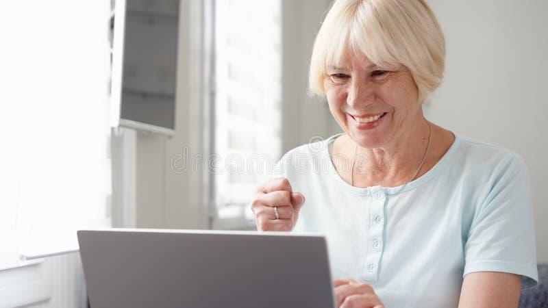 在家研究便携式计算机的年长资深白肤金发的妇女 愉快知道的好的消息激动和 免版税库存照片