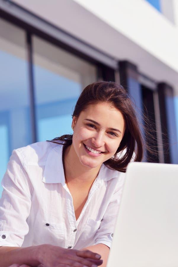 在家研究便携式计算机的轻松的少妇 免版税库存图片