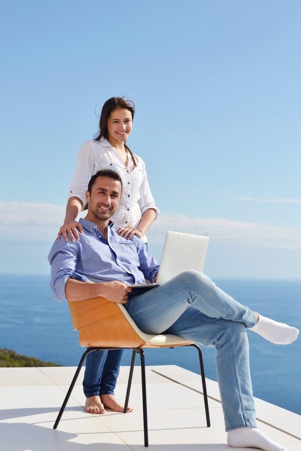 在家研究便携式计算机的轻松的年轻夫妇 图库摄影