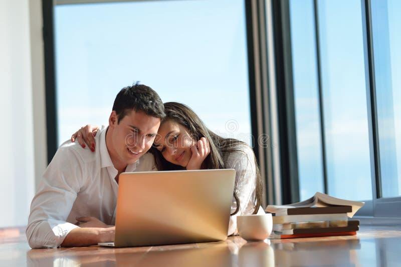 在家研究便携式计算机的轻松的年轻夫妇 库存图片