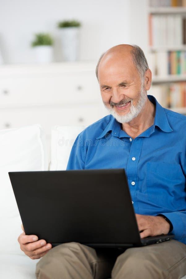 在家研究膝上型计算机的领抚恤金者 免版税库存照片