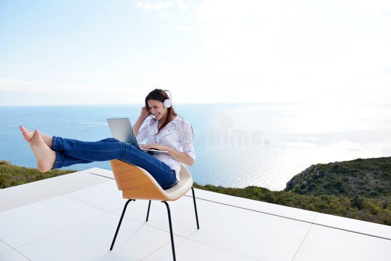 在家研究膝上型计算机的轻松的少妇 免版税库存照片