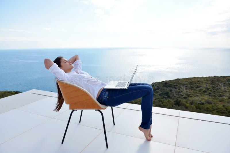 在家研究膝上型计算机的轻松的少妇 库存图片