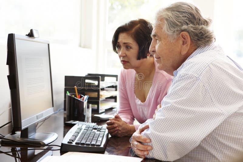 在家研究计算机的资深西班牙夫妇 免版税库存图片