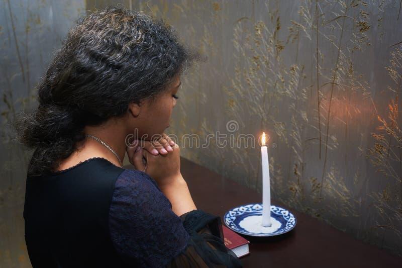 在家祈祷的非裔美国人的妇女在晚上 库存图片