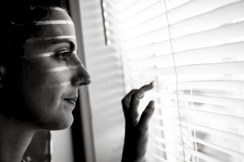 在家窗口附近的沮丧的少妇,特写镜头 库存图片