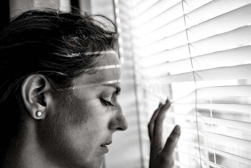 在家窗口附近的沮丧的少妇,特写镜头 免版税库存照片