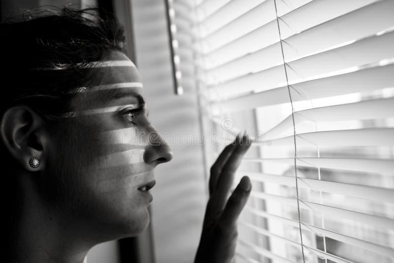 在家窗口附近的沮丧的少妇,特写镜头 库存照片