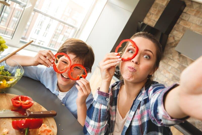 在家站立在厨房里的家庭一起拍看照相机的selfie照片做鬼脸盖面孔用甜椒 免版税图库摄影