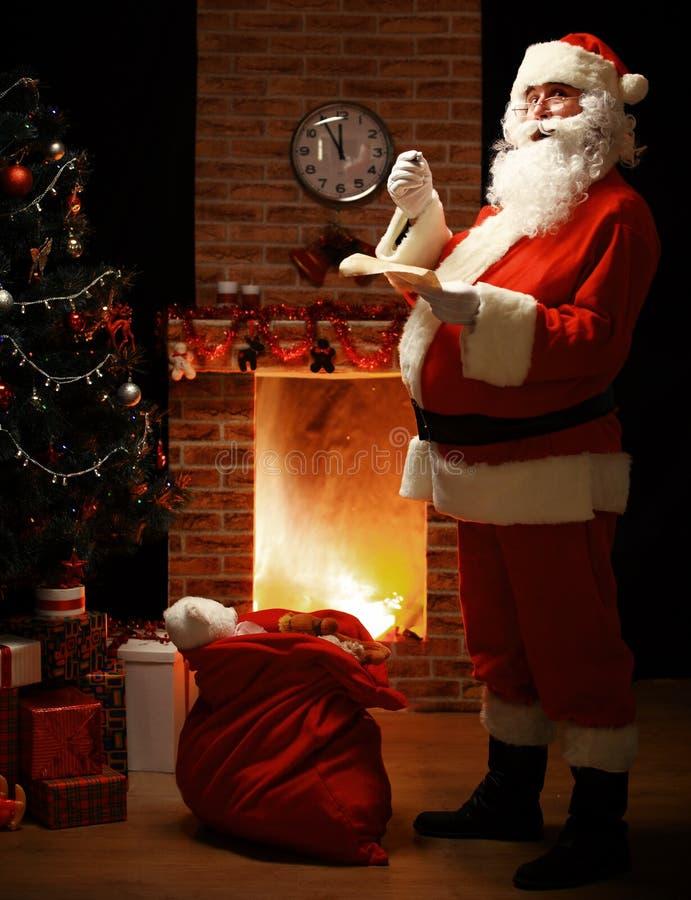 在家站立在他的室的愉快的圣诞老人画象 免版税图库摄影