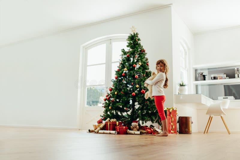 在家站立近的圣诞树的小女孩 免版税库存图片