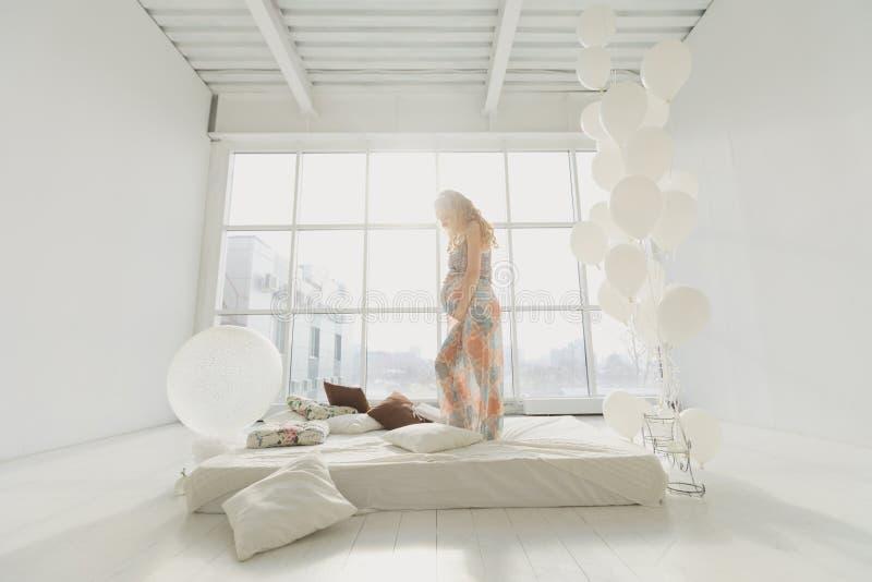 在家站立近的窗口的年轻美丽的孕妇 免版税库存图片