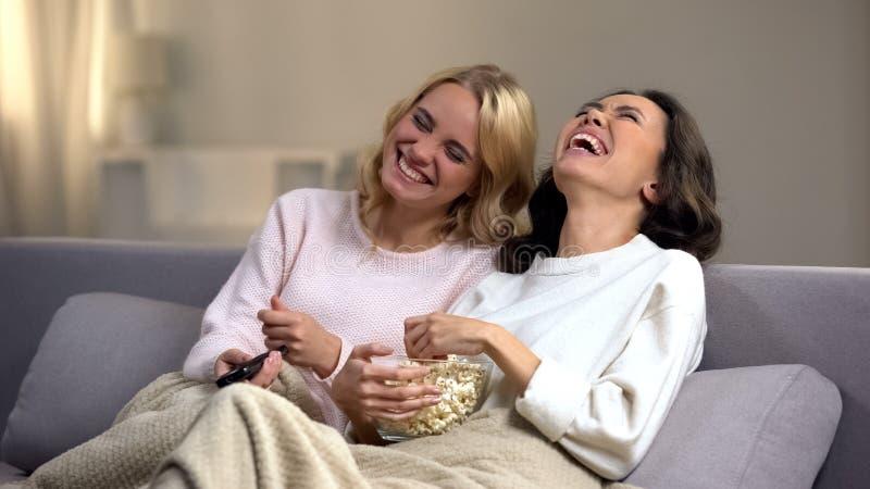 在家笑两的少女观看喜剧用玉米花和,悠闲时间 库存图片