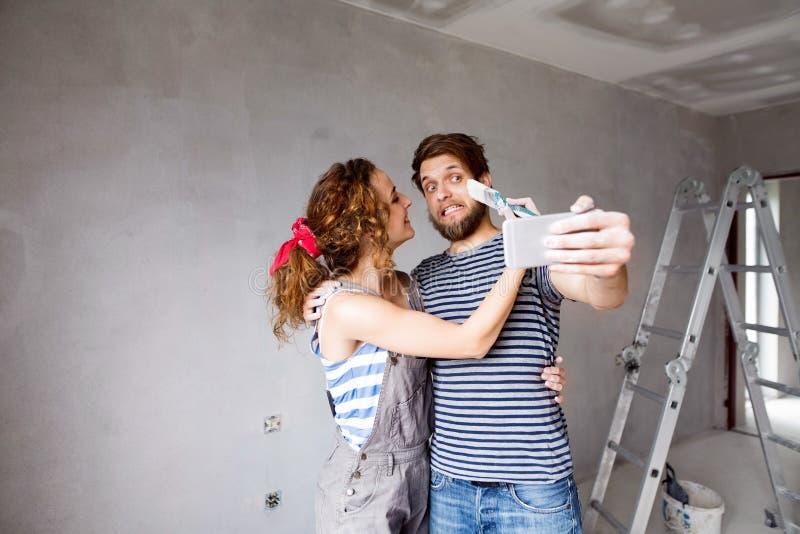在家结合绘的墙壁,采取与智能手机的selfie 免版税库存图片