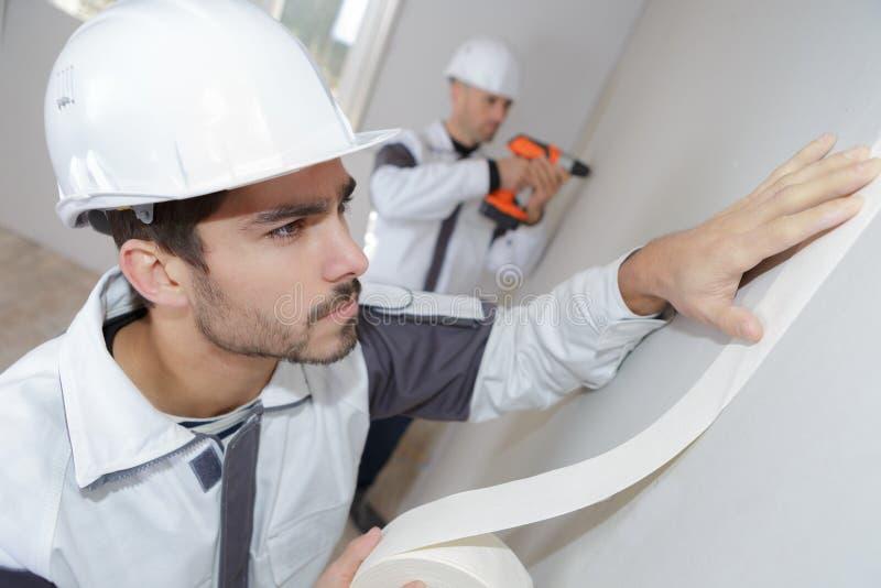 在家绘改善工作前的画家工作者保护的墙壁 库存图片