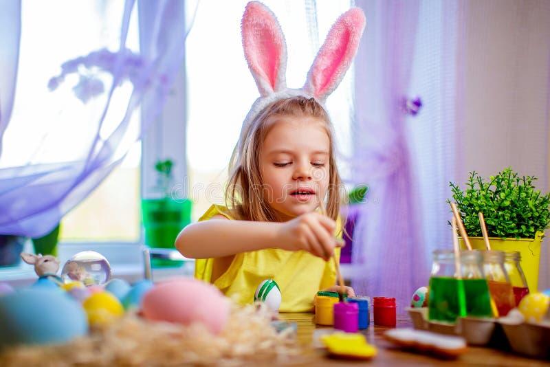 在家绘鸡蛋,小孩子的兔宝宝耳朵的愉快的复活节女孩 春天假日 免版税库存图片