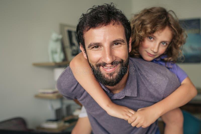 在家给他的儿子肩扛的愉快的父亲 图库摄影