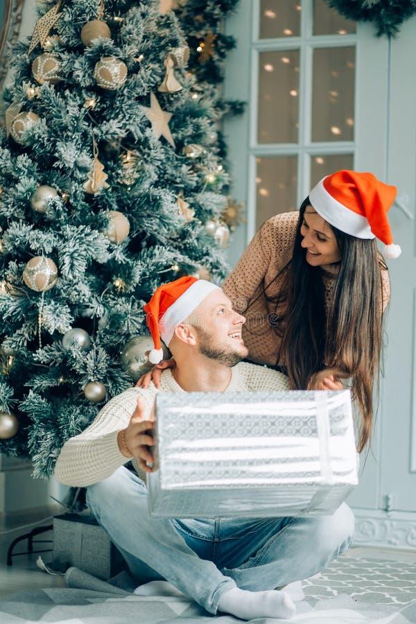 在家给她boyriend的英俊的妇女庆祝新年人的礼物 免版税库存图片