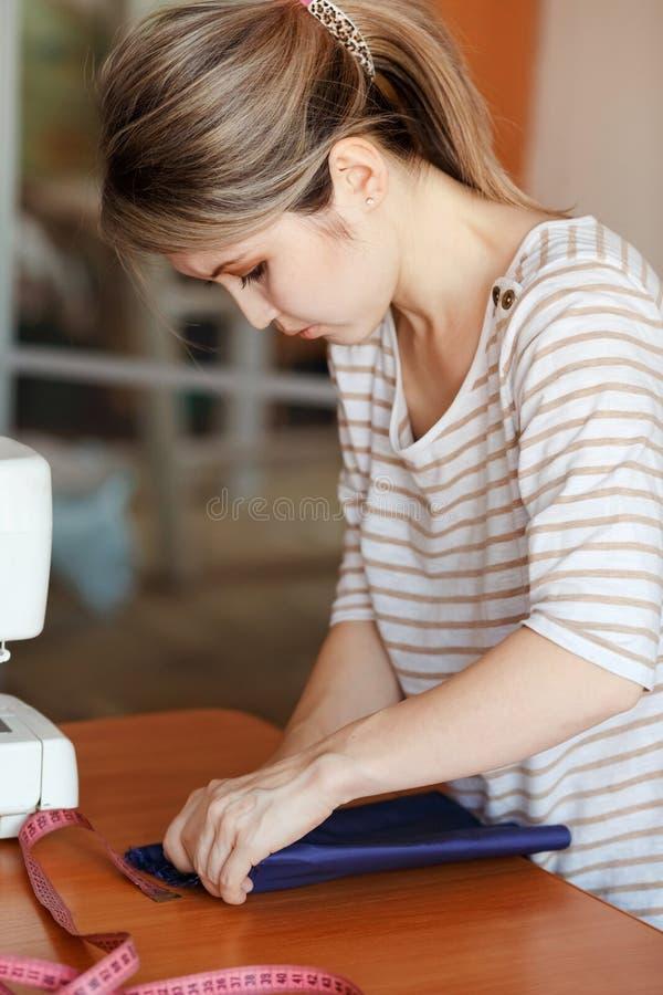 在家缝合的少妇,吊边蓝色织品 创造新的时兴的样式的时装设计师 裁缝通过广告做衣裳 库存图片