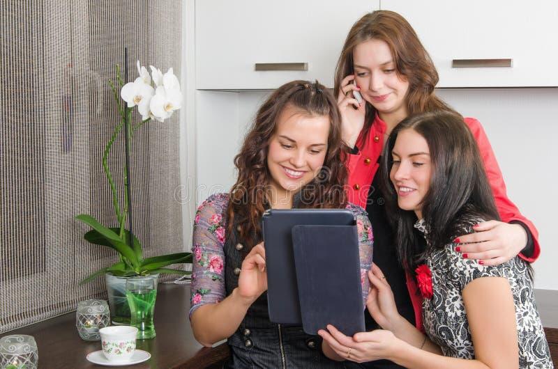 在家聊天和使用膝上型计算机的三个少妇朋友 免版税库存照片
