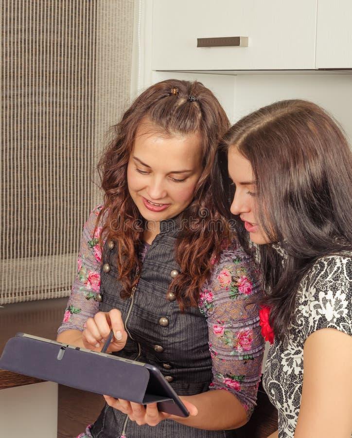 在家聊天和使用膝上型计算机的妇女朋友看新的p 免版税库存照片