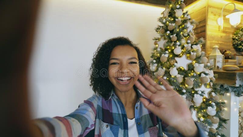 在家聊天网上交谈的年轻非裔美国人的女孩使用智能手机照相机在圣诞树附近 图库摄影