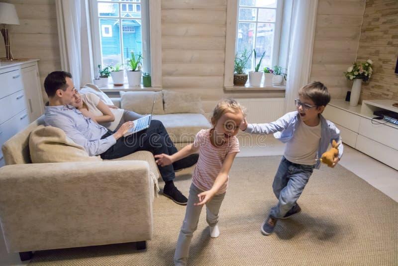 在家花费时间的愉快的家庭获得乐趣一起 图库摄影
