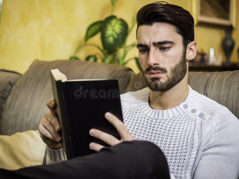 在家英俊的年轻人阅读书,在长沙发的开会 免版税库存照片