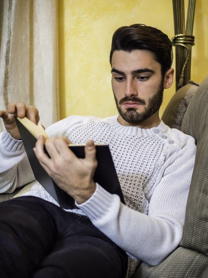 在家英俊的年轻人阅读书,在长沙发的开会 库存图片