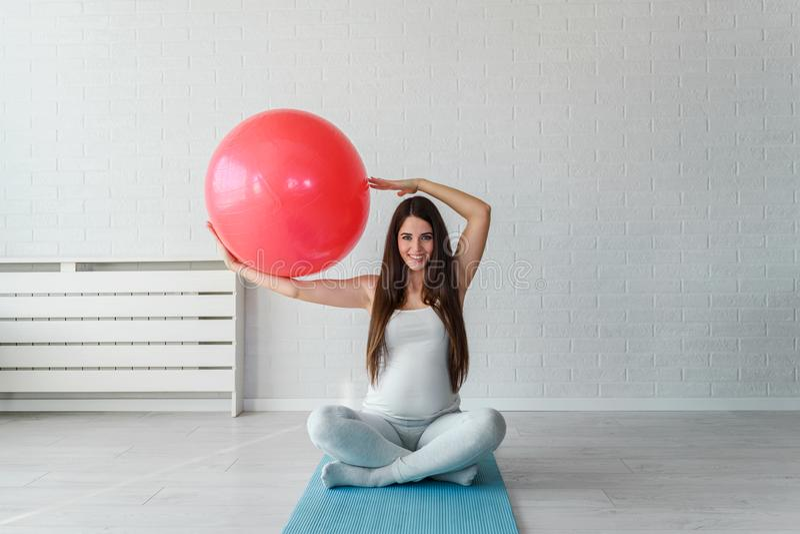 在家行使与pilates球的愉快的微笑的美丽的孕妇 库存图片