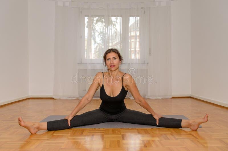 在家行使在席子的微笑的妇女瑜伽 免版税库存照片