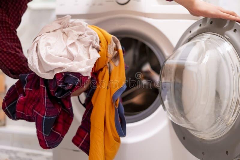 在家装载肮脏的衣裳的手的关闭入洗衣机卫生间f 免版税库存照片